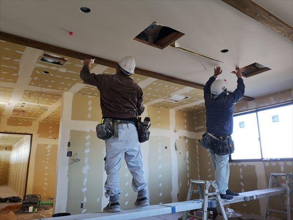 2階内装の天井仕上げ材を施す二人の内装職人