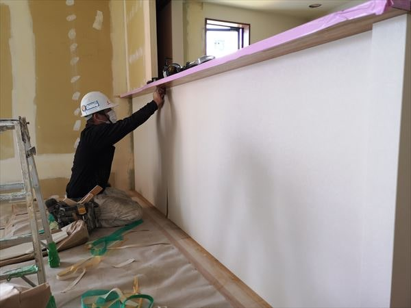 キッチン腰壁のクロス壁紙を張り込む職人
