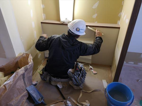 洗面台壁のクロスを張る内装職人