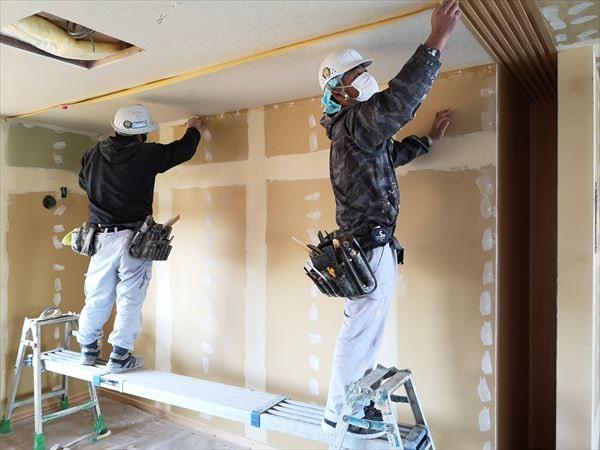 室内天井仕上げ壁紙を張り込む二人の職人