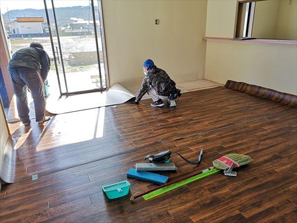 床仕上げシートを床に敷き込む内装職人
