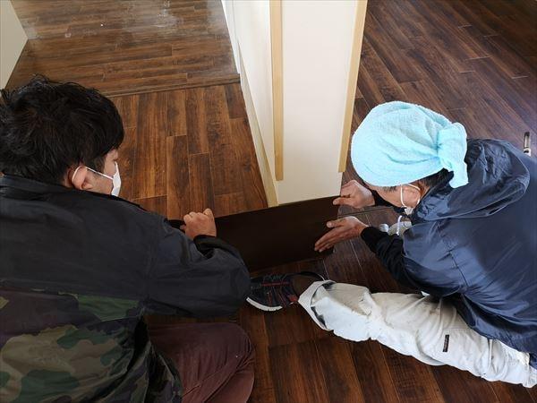 壁シート巾木を壁に張り込む二人の内装職人