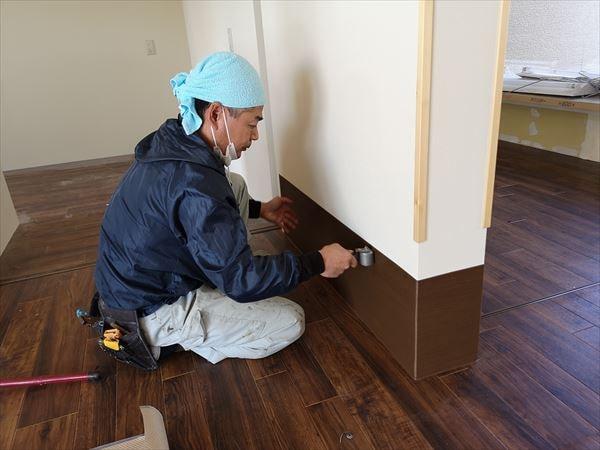 壁シート巾木をローラーで壁に馴染ませる内装職人