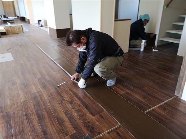 壁シート巾木の材料を計測する内装職人