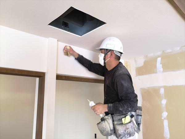 室内壁の仕上げ壁紙の張り込みを行う職人