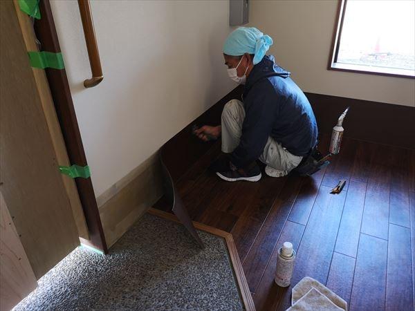 壁シート巾木を施工する内装職人