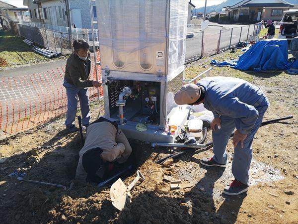 屋外でスプリンクラー専用の貯水タンクの配管工事を行う設備職人