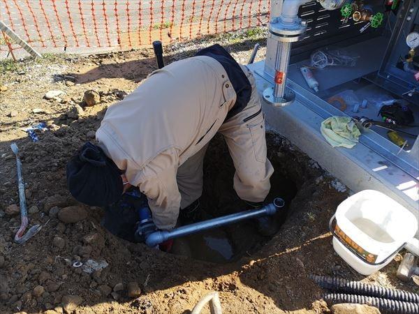 スプリンクラー専用ポンプの埋め込み配管を施す設備職人
