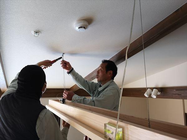 木製の造作照明器具を天井から設置する電気職人