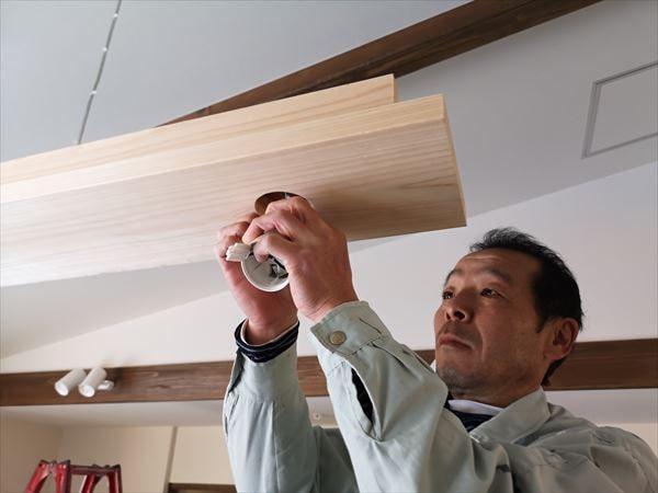 木製の造作照明に器具を取り付ける電気職人