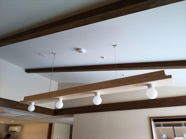 天井から吊り下げられた木製造作のランプ付き照明器具
