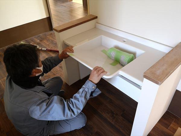 車椅子対応の白い洗面カウンターを設置する設備職人
