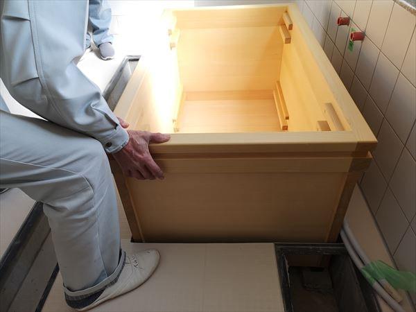 青森ヒバ製の浴槽を設置する現場監督