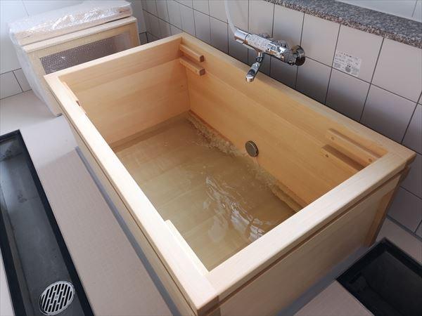 ヒバ製の木製浴槽にお湯を溜めている様子