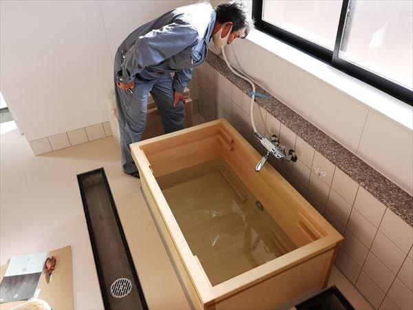 お湯を溜めた木製浴槽の周囲を確認する設備職人