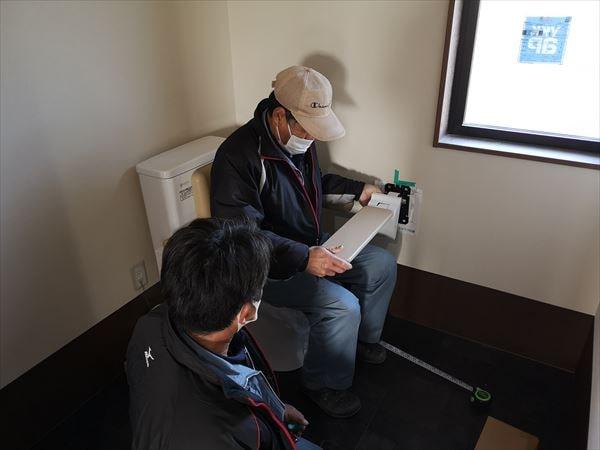 トイレ手すりの取り付け位置を確かめる設備職人