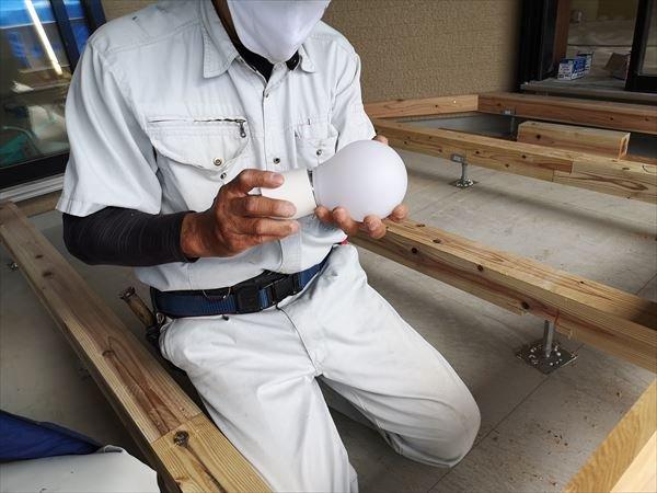 造作照明器具用に設置する白いボール型の電球を手にする棟梁