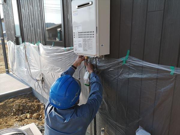 屋外壁掛け給湯ボイラーの配管を設置する設備職人