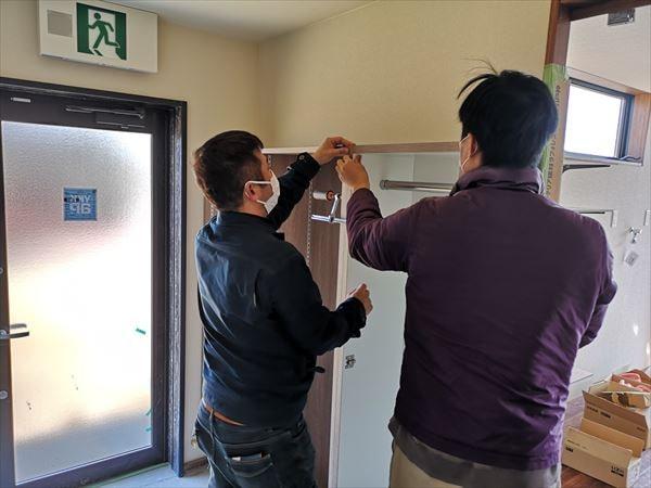 袖収納扉付きのオープン下足棚を設置する家具職人