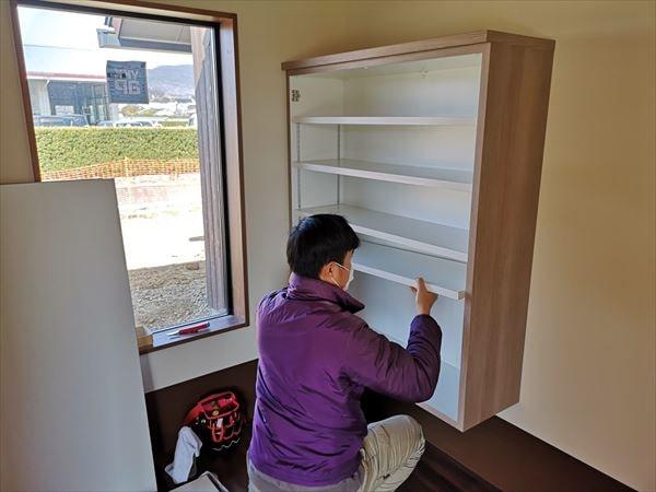 玄関下足収納の棚板を設置する家具職人