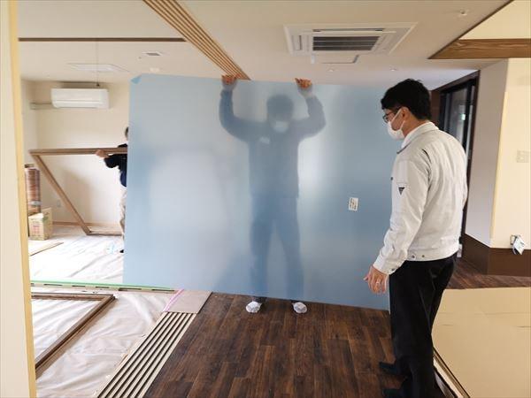 引き込み戸のポリカーボネイト板を運ぶ建具職人
