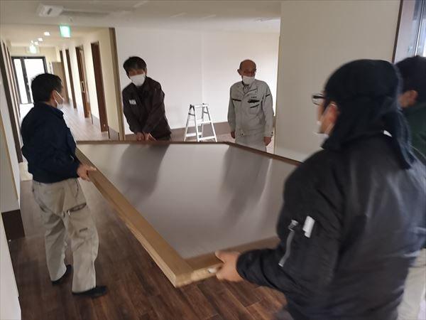 建て付け用の引き込み戸を運ぶ複数の建具職人