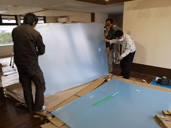 引き込み戸用のポリカーボネイト板を立ち起こす建具職人