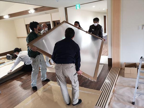 通路の引き込み建具を運ぶ4人の建具職人