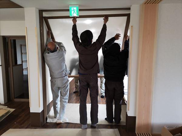 通路の引き込み建具を設置する監督と建具職人