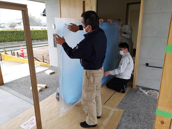 玄関引き込み戸の内部ポリカーボネイト板の保護ビニルを剥がす複数の建具職人