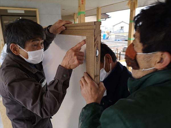 玄関引戸の内部ポリカーボネイト板の入れ込みを確認する建具職人