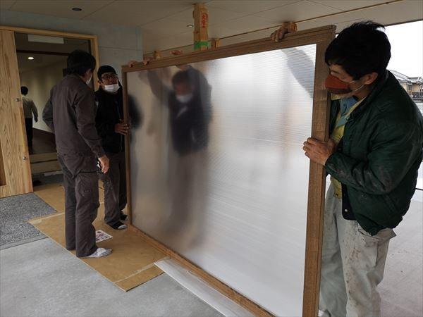 玄関引き込み戸の内部ポリカーボネイト板を設置する複数の建具職人
