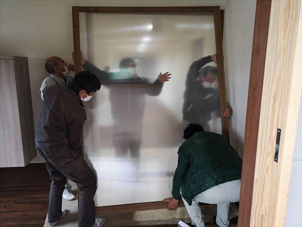 玄関引き込み戸の建て付けを行っている複数の建具職人