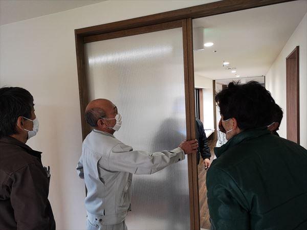 玄関引き込み戸の建て付け状況を確認する現場監督