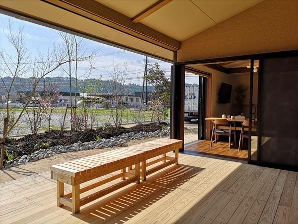 屋根と天井に覆われたインナー型のウッドデッキテラス デッキ先端にベンチが置かれ庭を楽しめる空間