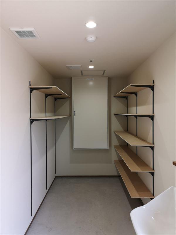 管理出口奥に設けられた器具倉庫 壁に可動用の収納棚を設け正面には電気の分電盤を設置