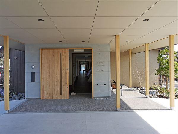 車寄せスペースから見たエントランス 木製の玄関引戸が開けられている