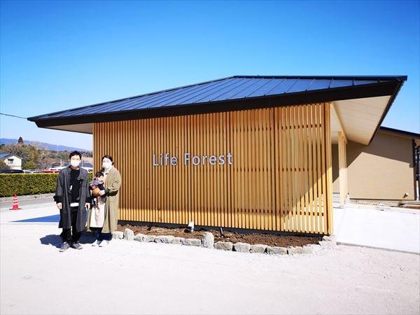 完成した新しい建物の前で記念撮影に応じるオーナー夫妻