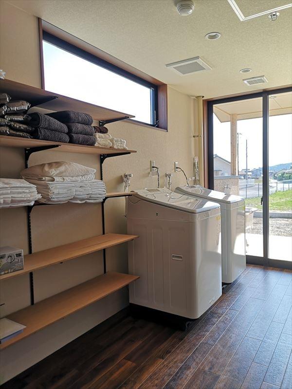 屋外物干しコーナーにつながる室内洗濯室の様子 壁付け棚に洗濯機2台を設置