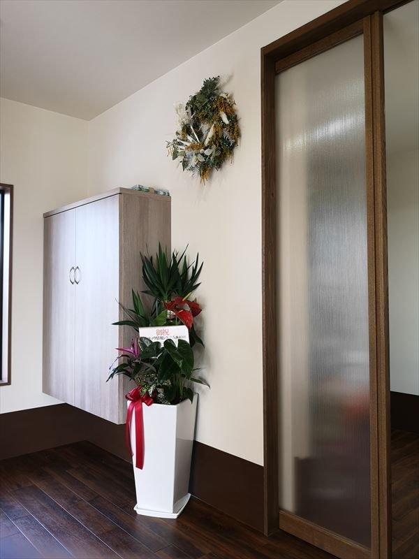 完成した玄関内部の様子 壁面に下足収納棚と飾り付けのリースと観葉植物
