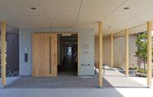 車寄せから見た玄関エントランス 木製の玄関戸と柱のある空間