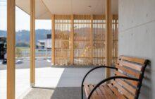 エントランス東側の休憩コーナー 木製ベンチ 遠方に木格子壁