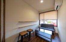 応接コーナー内観 黒い革張りのソファー1脚とガラスのテーブルが置かれる