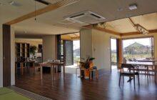 休憩室から見た通いスペースの内観 中央に屋外へ出入り可能なウッドデッキテラス