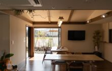通いスペースにある食堂コーナー ダイニングテーブル2脚 大きな引き込み窓 壁掛けテレビ