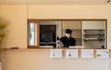 食堂から見たキッチン室 開閉収納可能の腰窓 キッチンで作業する管理栄養士さん