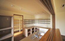 キッチンカウンターから見たキッチン内部 壁面に収納棚 キッチン奥に食品庫