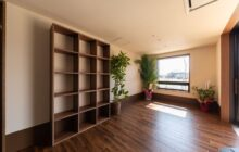 通いスペースにあるくつろぎコーナー 壁面にオープン型の収納棚 大きな窓から朝陽が射し込む