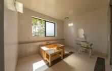 沐浴室内観 中央に檜葉の浴槽 壁面にシャワーコーナー