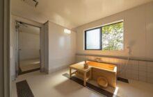 沐浴室内観 中央に檜葉の浴槽 窓から明るいひかりが射し込む